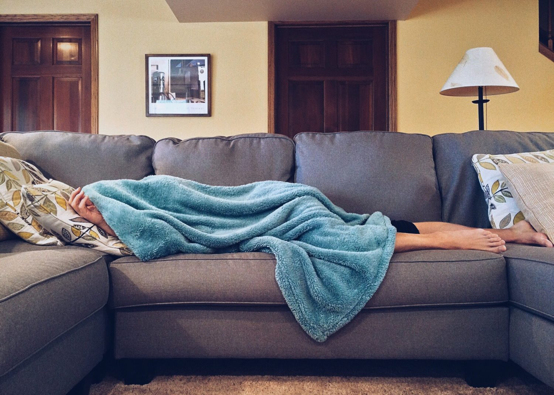 Mensch liegt unter Decke auf Couch.