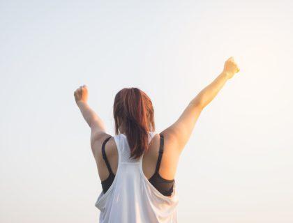 Frau streckt motiviert die Hände in die Luft