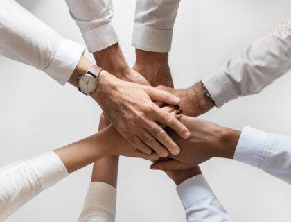 Menschen legen die Hände aufeinander.