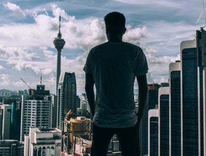 Mann schaut von oben auf Stadt