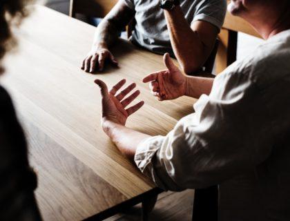Menschen die an Tisch sitzen