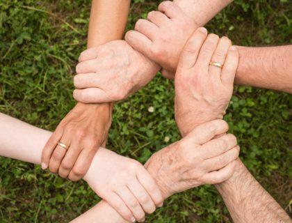 Menschen greifen sich an den den Händen