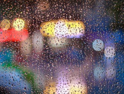 Fenster mit Regen und bunten Lichtern