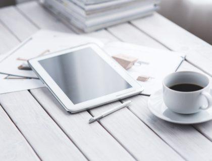 New Work Zitate, Symbolbild mit Tisch, auf dem Tablet und Kaffee stehen.